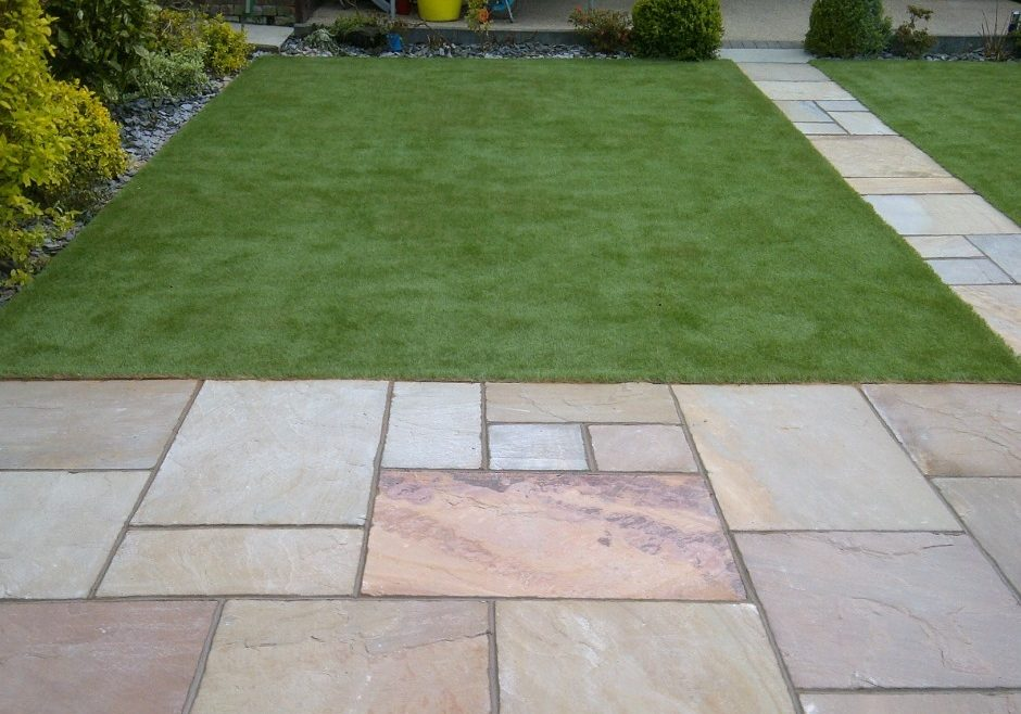 A picture of a path in the centre of two artificial grass lawns.